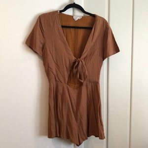 Brown romper with tie cutout.